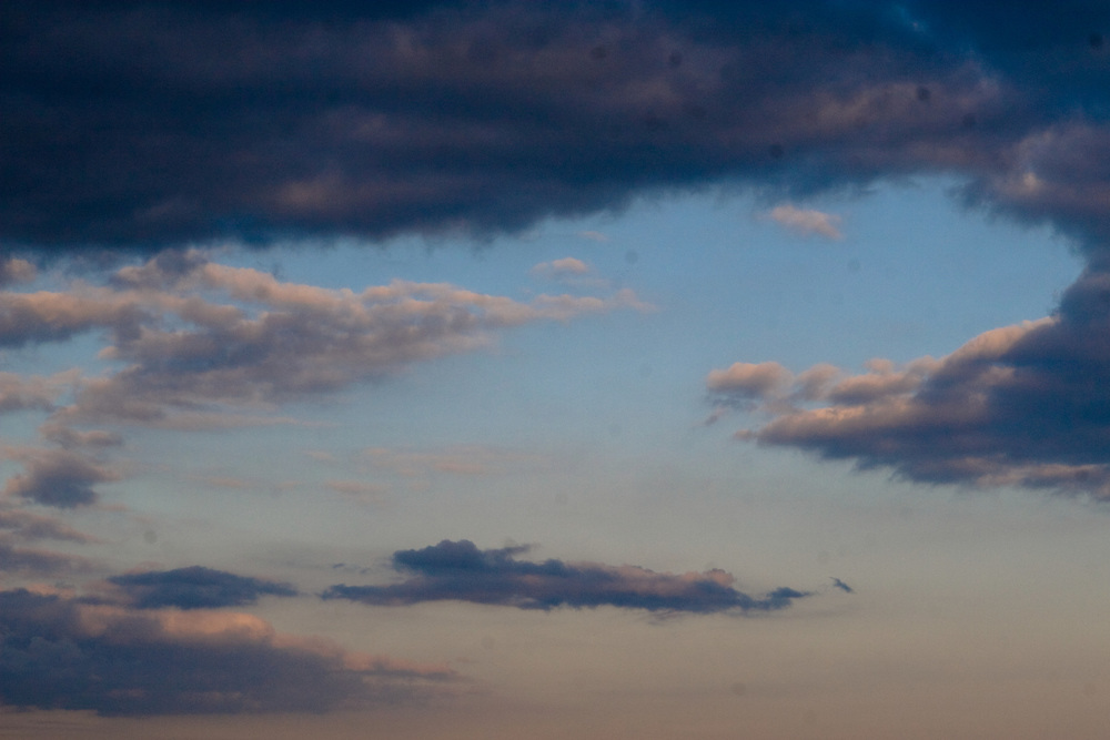 Fluffy clouds float on a pink and blue sky at dusk.