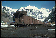RGS caboose #0400 on the tail of an eastbound freight in Telluride yard, headed for the mines and mills at Pandora.<br /> RGS  Telluride, CO  Taken by August, Irving - 4/15/1949<br /> Also at RDS079-057.<br /> Thanks to Don Bergman for additional information.