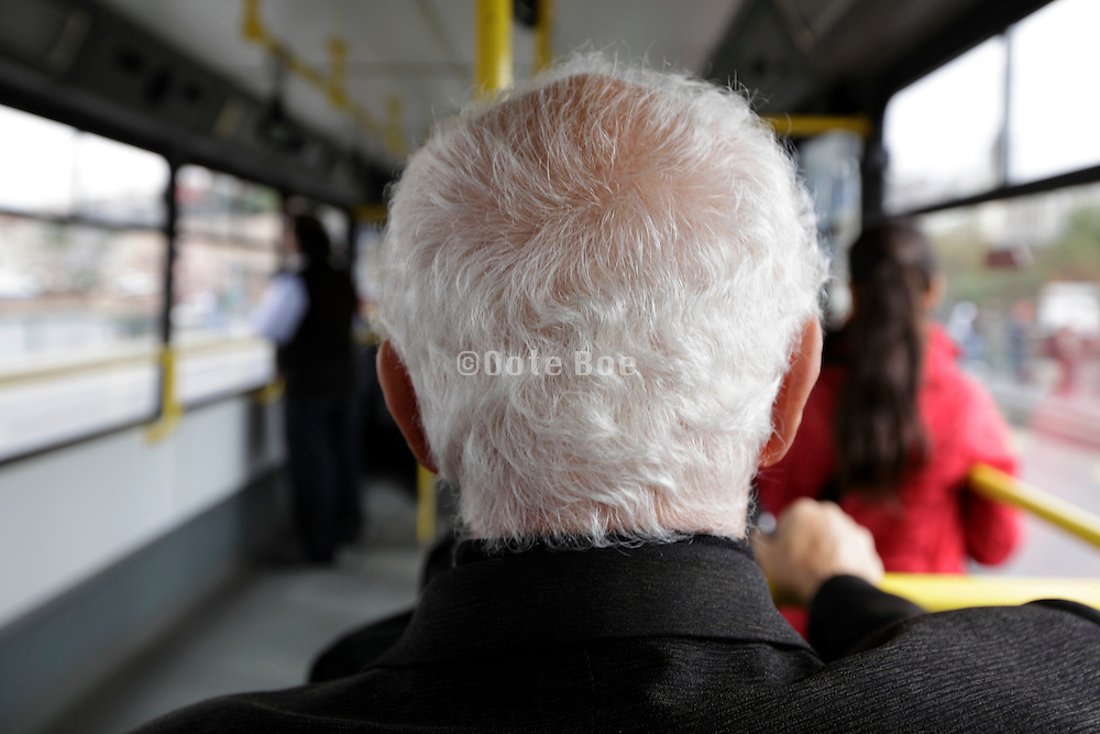 senior man with white hair sitting in a public bus
