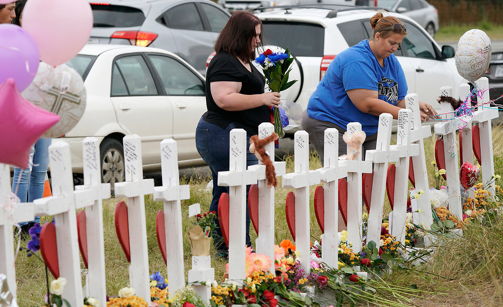 Charlene Uhl (L) brings flowers for her killed daughter Haley Krueger at crosses placed for those killed in the shooting at the First Baptist Church of Sutherland Springs, Texas, U.S.  November 10, 2017.  REUTERS/Rick Wilking