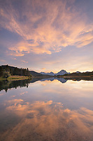 Clouds glowing red and orange in the light of the setting sun reflected in still waters of the Snake River at Oxbow Bend, Grand Teton National Park Wyoming