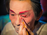 """06 DECEMBER 2015 - BANGKOK, THAILAND: A Chinese opera performer puts on his makeup before going on stage at the Ruby Goddess Shrine in the Dusit district of Bangkok. Chinese opera was once very popular in Thailand, where it is called """"Ngiew."""" It is usually performed in the Teochew language. Millions of Chinese emigrated to Thailand (then Siam) in the 18th and 19th centuries and brought their culture with them. Recently the popularity of ngiew has faded as people turn to performances of opera on DVD or movies. There are about 30 Chinese opera troupes left in Bangkok and its environs. They are especially busy during Chinese New Year and Chinese holidays when they travel from Chinese temple to Chinese temple performing on stages they put up in streets near the temple, sometimes sleeping on hammocks they sling under their stage.     PHOTO BY JACK KURTZ"""