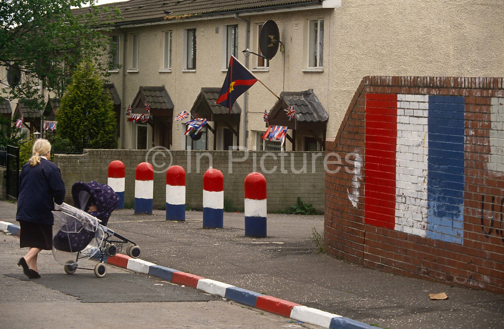 A mother crosses the road towards Loyalist colours painted on the streets in a Protestant area of Belfast, on 7th June 1995, in Belfast, Northern Ireland, UK.
