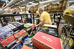 Embargoed to 0001 Friday November 16 Workers pack trainers, shoes and footware at Amazon's fulfillment centre in Swansea, in the run up to Black Friday.