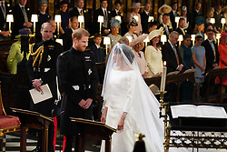 Prince Harry looks at his bride, Meghan Markle, as she arrives accompanied by the Prince of Wales in St George's Chapel at Windsor Castle for their wedding.