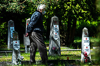 Bialystok, 09.05.2020. 75. rocznica zakonczenia II Wojny Swiatowej na cmentarzu zolnierzy radzieckich. Uroczystosc Dnia Zwyciestwa zostala zorganizowana przez Rosyjskie Stowarzyszenie Kulturalno-Oswiatowe. Ze wzgledu na epidemie koronawirusa w uroczystosci wzielo udzial kilkanascie osob. N/z uczestnicy uroczystosci zapalaja znicze przy mogilach zolnierzy radzieckich fot Michal Kosc / AGENCJA WSCHOD