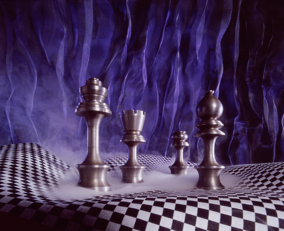 Solid steel chess pieces in surreal environment. Royal blue or purple pleated back drop behind a black and white checkered chess table that is wavy checker board across the page with smoke swirling around the chess pieces.