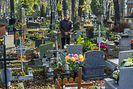 A man remembers his deceased loved one at Rakowicki Cemetery in Krakow, Poland in 2019.