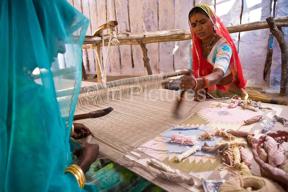 Indian women weaves a dhurrie on a traditional loom using a typical geometric pattern using a interlocking technique, Salawas, Rajasthan, India.