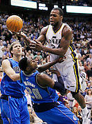 Utah Jazz power forward Paul Millsap (24) is fouled by Dallas Mavericks center Ian Mahinmi (28) as Mavericks forward Dirk Nowitzki, left, of Germany also defends during the second half of an NBA basketball game, Monday, April 16, 2012, in Salt Lake City. The Jazz defeated the Mavericks in triple overtime 123-121.  (AP Photo/Colin E Braley).