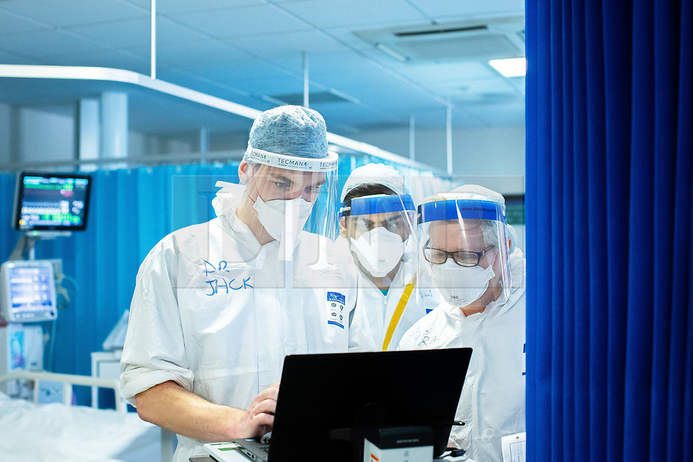 © Licensed to London News Pictures. 05/02/2021. Oldham , UK . Clinicians review a patient's treatment during a ward round . Inside Royal Oldham Hospital's Covid ITU where patients, most of them unconscious , are treated for the effects of Coronavirus . Photo credit : Joel Goodman/LNP