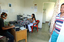 """Davis Semeco, left, plays music as Rosa Amarista, middle , hosts their radio show on """"A New Day Radio"""", a community radio station in Caracas.  Sandino Pena, a community member stands in the foreground.  The station operates out of the home of Zulay Zerpa, who donates the space 7 days a week between 3pm and 9pm.  Chavez and his government have been increasingly supportive of these generally Chavista community media stations as a response to the anti-chavista private media."""