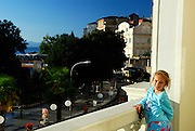 Child (9 years old) dressed in pyjamas, leaning on hotel balcony in early morning sunlight, overlooking street in Opatija, Croatia