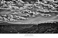 20x30 poster print of mountains with sunlight and storm clouds.