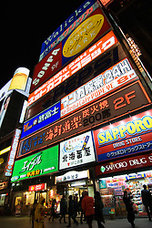 Many illuminated advertising signs and billboards at night in Susukino district of Sapporo Japan