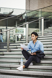 July 25, 2017 - Businessman wearing blue shirt sitting outdoors on steps, holding digital tablet and papers. (Credit Image: © Mint Images via ZUMA Wire)
