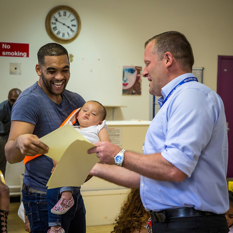 A young father receiving a certificate from the prison governor for passing a fatherhood course during a family visit in HMP Brixton, South London on the 26th of July 2016, London United Kingdom. The Prisoner Advice & Care Trust (PACT) organise family training and special family days that help the men inside the prison connect with and support their partners and children on the outside. (photo by Andy Aitchison)