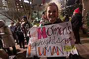 """A young woman holds a sign saying """"Women's Rights Are Human Rights"""" at protest march by members of the Democratic Party Abroad organisation to mark the inauguration of President Donald Trump, Tokyo, Japan. Friday January 20th 2017 Around 400 people took apart in the march, which started in Hibiya Park at 6:30pm and finished in Roppongi just before 8pm, to honour the service given by President Obama and to protest against the illiberal policies expected of the new administration of President  Trump."""