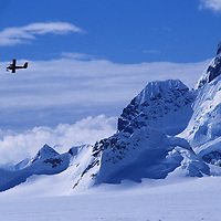 """A Twin Otter ski plane flies over Calley Glacier and a crag called """"Wiltsie's Peak"""" on the Antarctic Peninsula."""