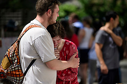 © Licensed to London News Pictures. 17/06/2017. London, UK. Emotional members of the public looks at floral tributes left for the victims of Grenfell tower block in west London following a devastating fire earlier this week. The blaze engulfed the 27-storey building killing 12 - with 34 people still in hospital, 18 of whom are in critical condition. The fire brigade say that they don't expect to find anyone else alive. Photo credit: Ben Cawthra/LNP