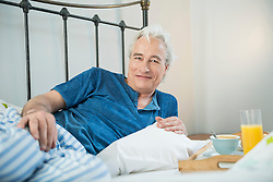 Portrait of mature man having breakfast in bed, smiling