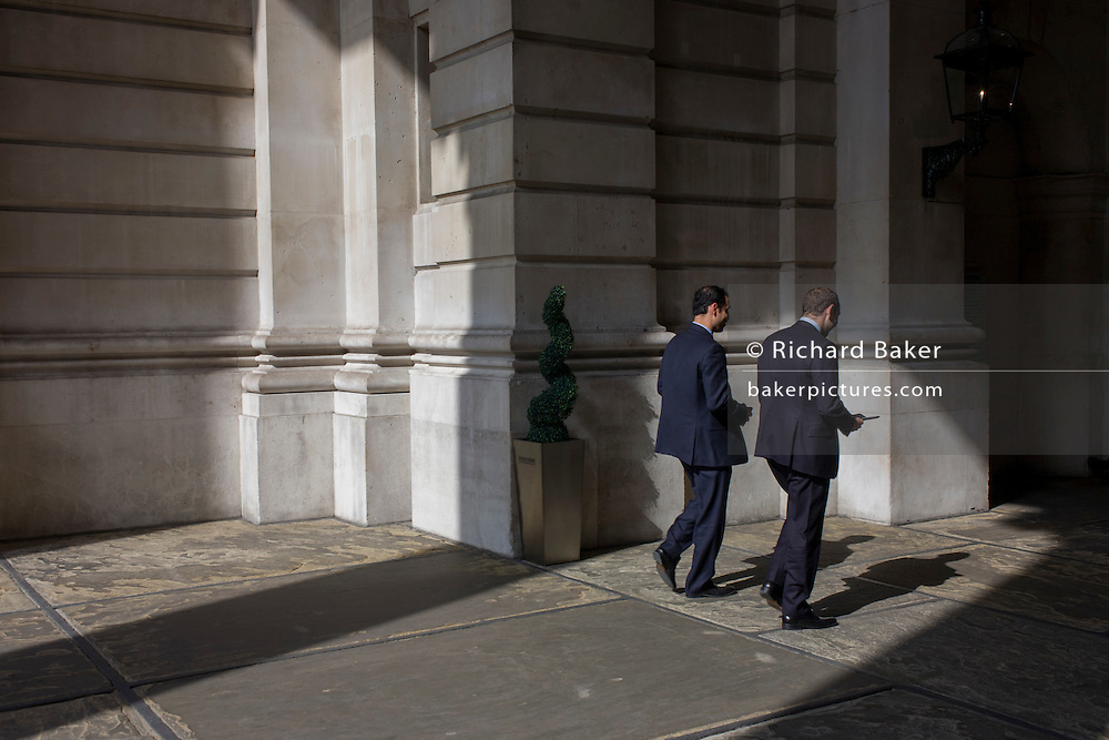 Businessmen walk through sunlight at Cornhill in the City of London.