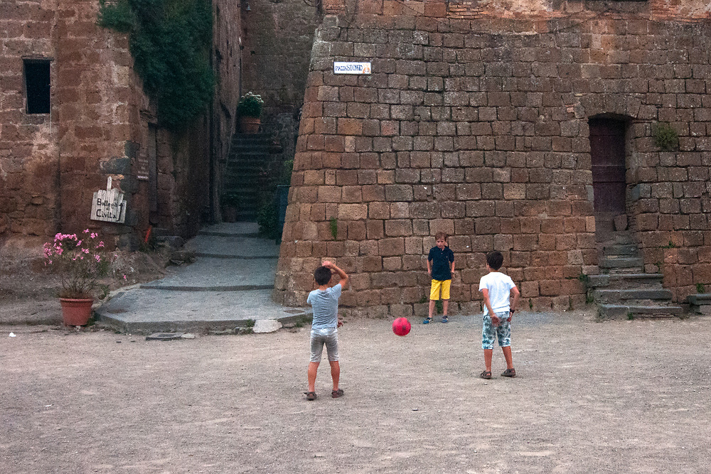 """Children play in San Donato square in the village of Civita di Bagnoregio.<br /> Civita di Bagnoregio is a town in the Province of Viterbo in central Italy, a suburb of the comune of Bagnoregio, 1 kilometre (0.6 mi) east from it. It is about 120 kilometres (75 mi) north of Rome. Civita was founded by Etruscans more than 2,500 years ago. Bagnoregio continues as a small but prosperous town, while Civita became known in Italian as La città che muore (""""The Dying Town""""). Civita has only recently been experiencing a tourist revival. The population today varies from about 7 people in winter to more than 100 in summer.The town was placed on the World Monuments Fund's 2006 Watch List of the 100 Most Endangered Sites, because of threats it faces from erosion and unregulated tourism."""