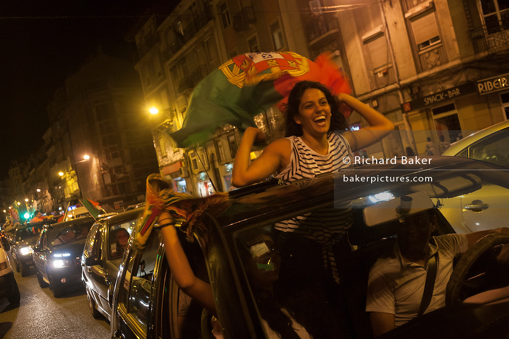 A girl Portuguese football fan celebrates her country's victory over France in the Euro 2016 tournament final on 10th July 2016, in Lisbon, Portugal. Waving their national flag above their heads, they wave to passers-by after the final whistle in the game that captivated Portugal with their hero, Christiano Ronaldo the symbol of their well-being and patriotism. (Photo by Richard Baker / In Pictures via Getty Images)