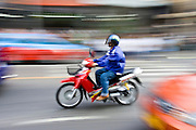 Commuter travelling on a scooter, Bangkok, Thailand