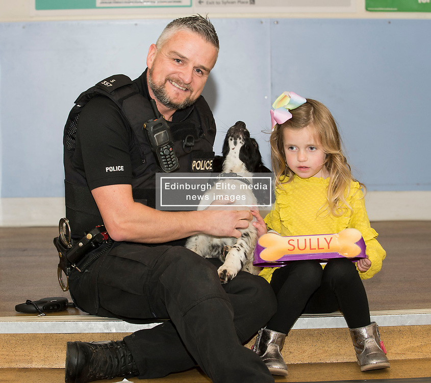Four year old Heidi Wilkie from Prestonpans with new police dog puppy Sully and his handler PC Richard Smith, at the Royal Hospital for Sick Children in Edinburgh, where she was one of the patients who chose the names for 12 week old Springer Spaniels Banjo and Sully, the two newest members of Police Scotland's dog section.  <br /> © Dave Johnston/ EEm