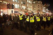 Police march up through Regents Street. The March of a Million Masks brought thousands of mostly masked protestors onto the streets of London. The march was in protest against the current govenrment and global internet state surveillance, and was held at Guy Fakes Night and called by the hacker group Anonymous.