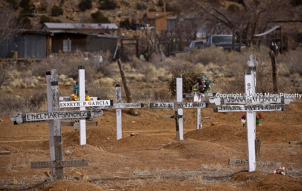 """SHOT 1/22/09 1:20:59 PM - Wooden crosses mark gravesites in a small cemetery on the Acoma Pueblo in New Mexico. Acoma Pueblo, Haak'ooh in Navajo, also known as """"Sky City"""", is a Native American pueblo built on top of a 367-foot (112 m) sandstone mesa in the U.S. state of New Mexico. The Pueblo, believed to have been established in the twelfth century or even earlier, was chosen in part because of its defensive position against raiders. It is regarded as the oldest continuously inhabited community in the United States..(Photo by Marc Piscotty / © 2009)"""