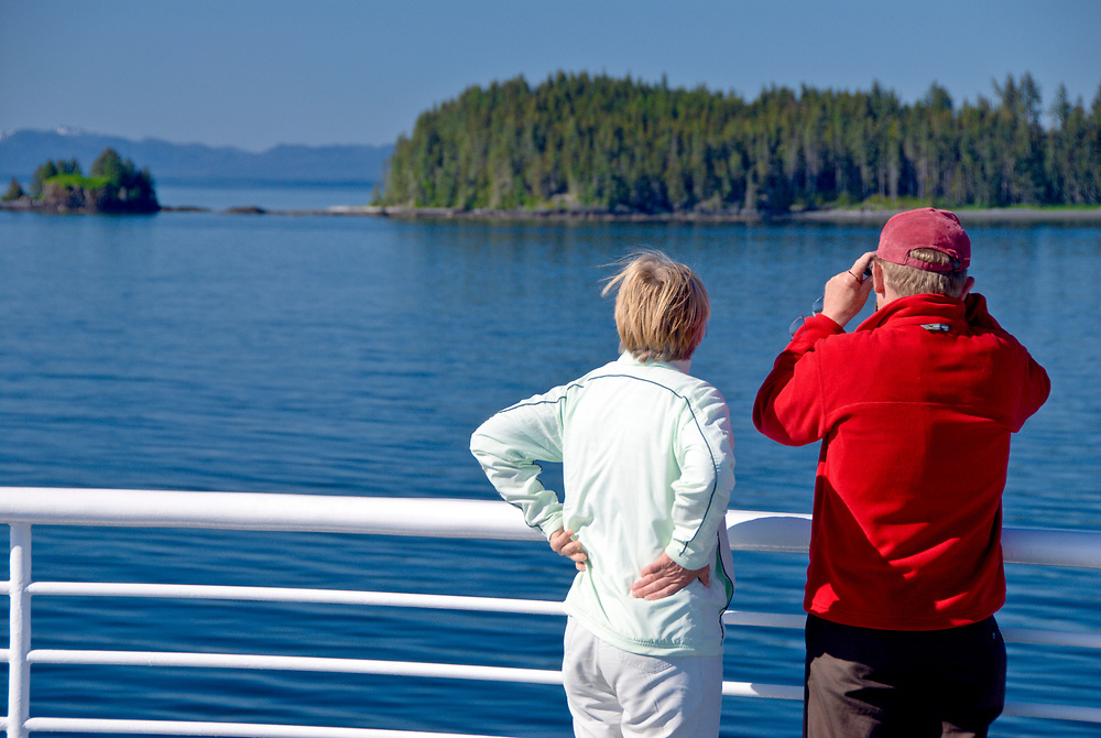 Passengers aboard the Alaska Marine Highway Ferry system  enjoy watching unspoiled coastal scenery and wildlife viewing at the railing.