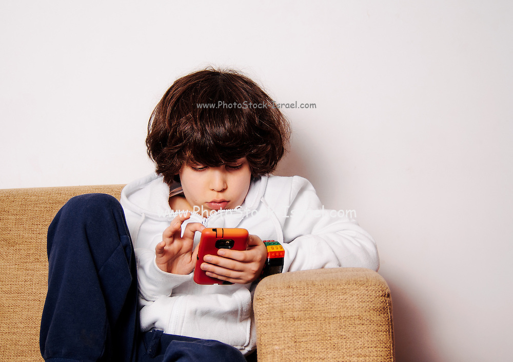 elementary school boy engrossed in a game on a mobile phone on the sofa