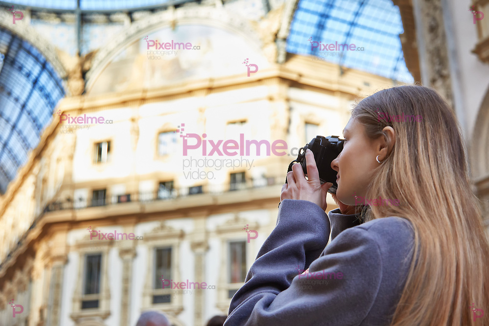 Tourist girl takes a photo in Galleria Vittorio Emanuele II during the day in Milan Italy