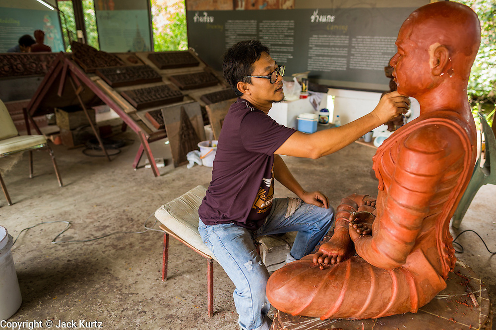 16 JULY 2014 - SAMUT PRAKAN, SAMUT PRAKAN, THAILAND: An artisan works on a statue of the Buddha at Ancient Siam. Ancient Siam is a historic park about 200 acres (81 hectares) in size in the city of Samut Prakan, province of Samut Prakan, about 90 minutes from Bangkok. It features historic recreations of important Thai landmarks and is shaped roughly like the country of Thailand.      PHOTO BY JACK KURTZ