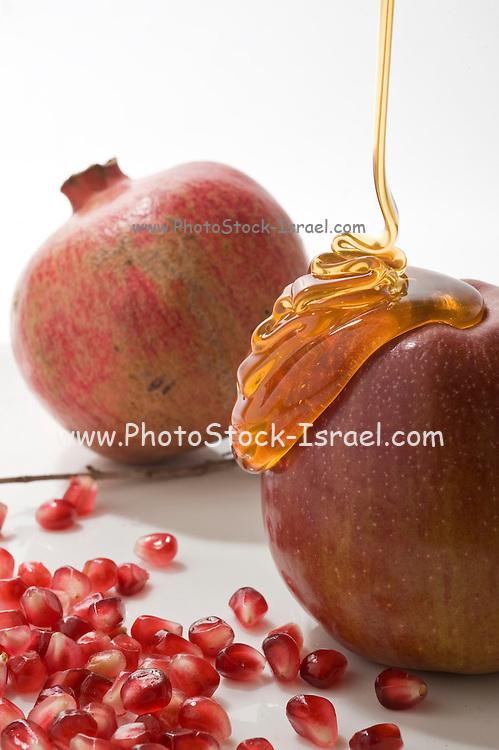 Apple pomegranate seeds, and honey Symbols of Roah Hashanah the Jewish New Year on white background