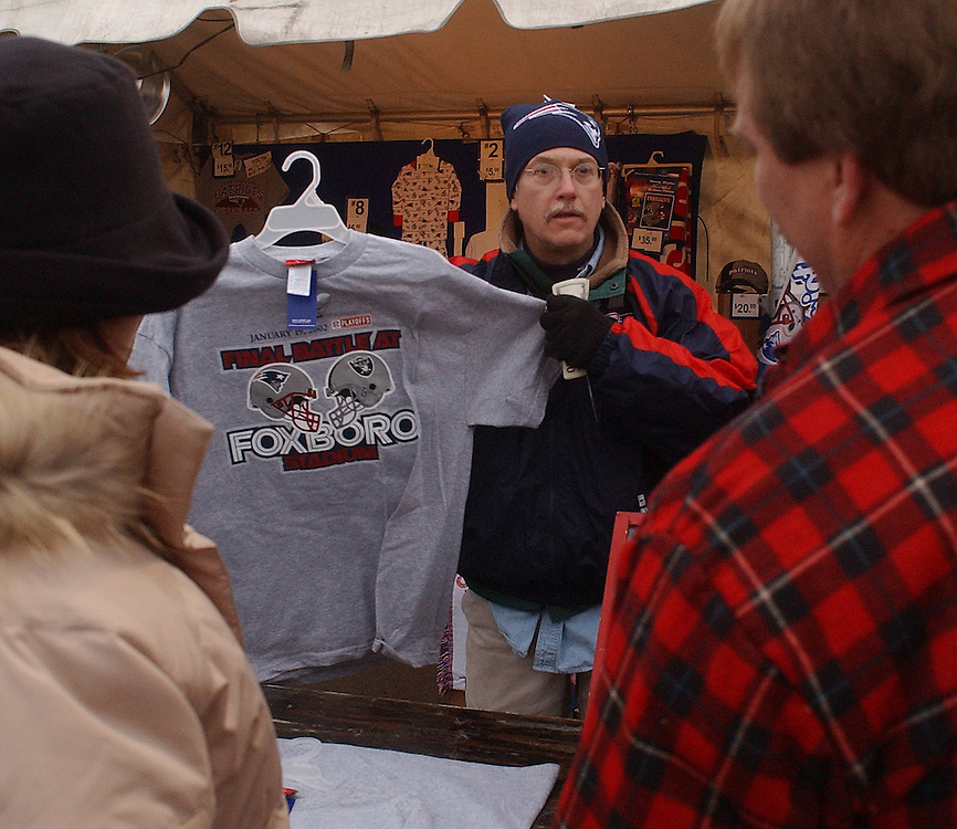 (1/19/02 Foxboro, MA) Patriots vs. Raiders at Foxboro Stadium. Jack Drinkwater shows a t-shirt to fans as the head into the game.  O'CONNER STORY> (011902patsmjs.JPG- Staff Photo by Michael Seamans. Saved in Sunday/FTP)