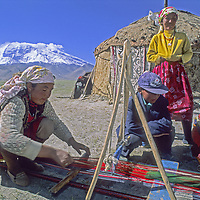 A nomadic Kyrgyz woman weaves on a home made loom outsider her family's akoi (yurt) in the Pamir Mountains of Xinjiang Province in far western China.  24,750-foot [Mount] Mustagh Ata rises in the background.