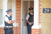 © Licensed to London News Pictures. 23/04/2014. New Malden, UK. A police office exits the house. The scene in New Malden where a woman has been arrested after the discovery of three bodies of children in a house overnight. Photo credit : Stephen Simpson/LNP