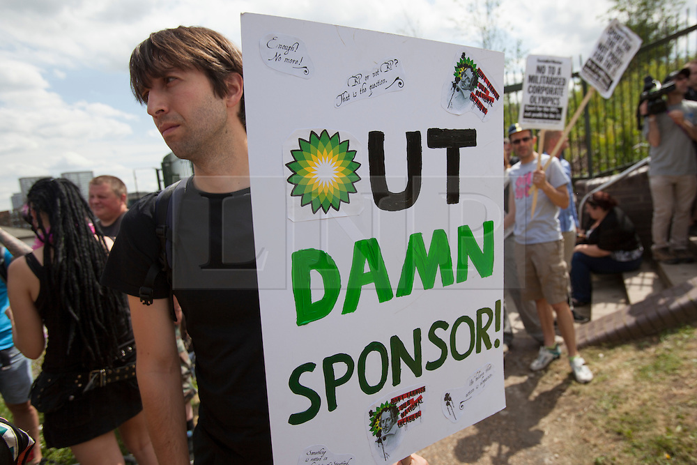 © licensed to London News Pictures. London, UK 28/07/2012. A protester posing with a placard against BP as anti-Olympics protesters gathering in Mile End Park to march to Victoria Park in order to protest against the greed of the Olympic sponsors. Photo credit: Tolga Akmen/LNP