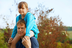 Father Carrying Daughter on Shoulders Outdoors