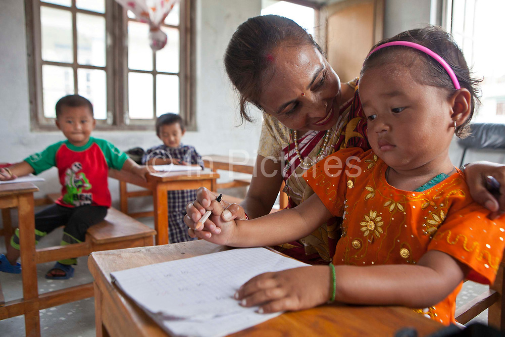 A female Nepalese teacher  encourages a young girl student to learn how to write as two boys watch and wait. They are in a nursery class room at the GoodWeave centre in Attarkhen, Kathmandu, Nepal.  They are children of carpet factory workers, and have been supported into education by GoodWeave, a charity that works towards getting children out of factories and into education.  Previously these children would have been left unattended in the factory while their parents worked as their low salary could not cover childcare costs. GoodWeave were recipients of the Stars Foundation's Impact Award.