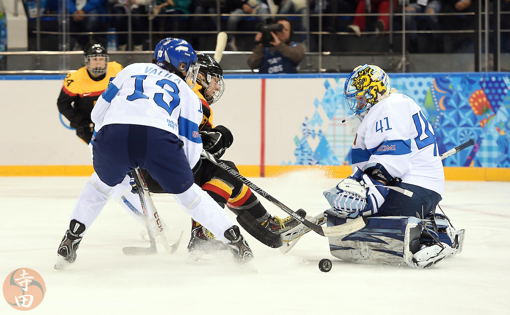 Feb 16, 2014; Sochi, RUSSIA; Finland goalkeeper Noora Raty (41) makes a save against Germany forward Nina Kamenik (7) as Finland forward Rikka Valila (13) defends in the women's ice hockey classifications round during the Sochi 2014 Olympic Winter Games at Shayba Arena.
