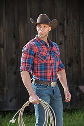 Rugged hot cowboy with a lasso by a barn