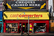 Street view of a high-street cash converters shop in Lewisham, South London, United Kingdom.  A few people are waiting outside the shop and one man is looking at the jewelry section of the window display.  This is a pawn shop which also cashes cheques.