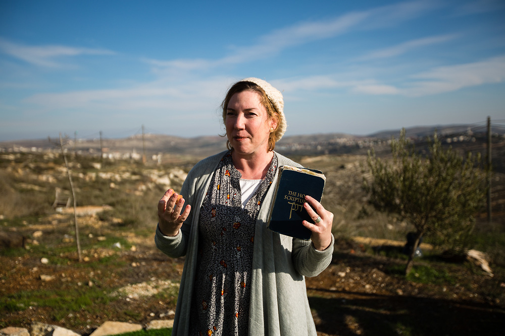 Eliana Passentin talks as she hold a Bible outside her bed and breakfast 'Warm Home with a Breathtaking View' which is advertised on Airbnb international home-sharing site and rental listings service, in the West Bank Jewish settlement of Eli, on January 28, 2016.