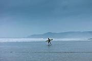 Surfer walking along the beach at Woolacombe, North Devon, UK
