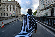 A supporter of the Black Lives Matter movement is wrapped in black American flag and chants slogans during a protest at Waterloo Bridge in central London, Saturday, June 13, 2020. British police have imposed strict restrictions on groups protesting in London Saturday in a bid to avoid violent clashes between protesters from the Black Lives Matter movement, as well as far-right groups that gathered to counter-protest. Anger against systemic levels of institutional racism has raged through the city, and worldwide; sparked by the death of George Floyd, who was killed in Minneapolis, US, by a policeman who restrained him with force on 25 May 2020. (Photo/ Vudi Xhymshiti)