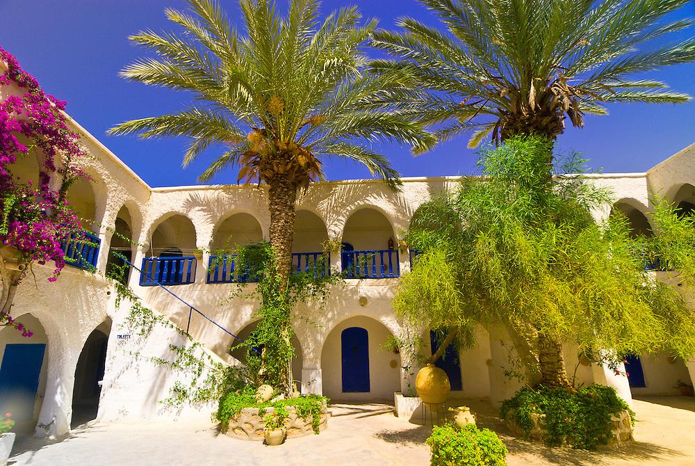 Magenta flowers drape a Djerba Island cortyard, Djerba Island, Tunisia